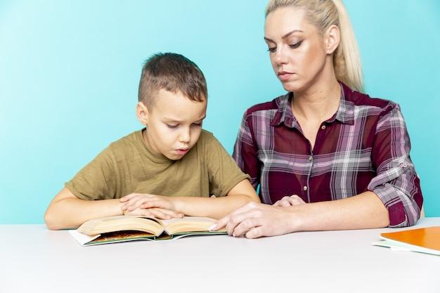 Mère aidant son fils à faire ses devoirs sur fond rose isolé. l'éducation à distance.