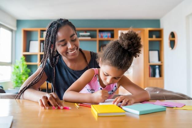 Mère aidant et soutenant sa fille avec l'école à la maison tout en restant à la maison. nouveau concept de mode de vie normal.
