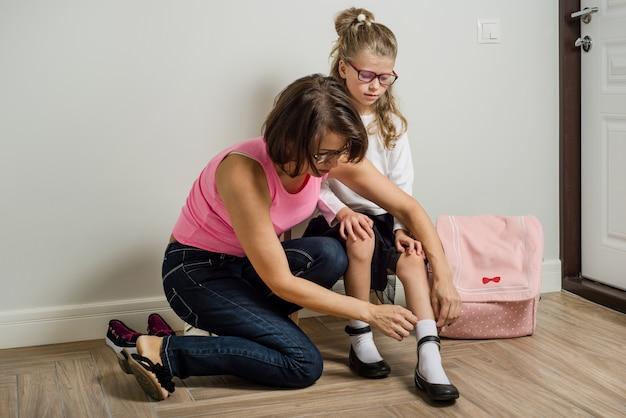 Une mère aide à mettre des chaussures aux pieds de sa fille