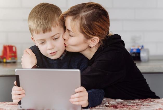 Mère à l'aide d'un ordinateur portable et d'une tablette d'enseignement avec son fils en ligne à la maison dans sa chambre