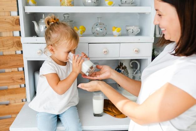 Mère aider sa fille à boire du lait