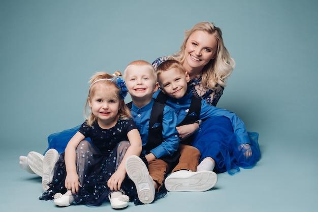 Mère aimante embrassant leurs trois enfants