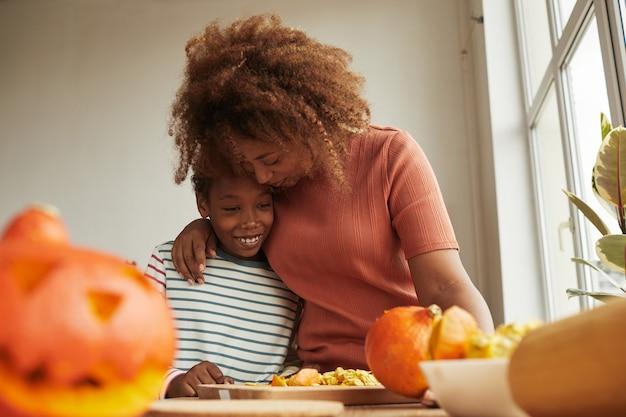 Mère aimante embrassant son fils joyeux tout en découpant des citrouilles mûres pour la fête d'halloween ensemble