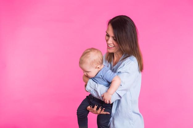 Mère aimante jouant avec son petit garçon sur rose.