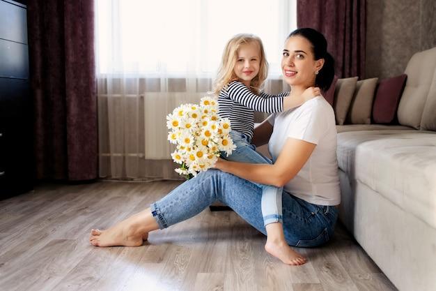 Mère aimante et petite fille à la maison avec un bouquet de marguerites. la famille passe un bon moment ensemble.