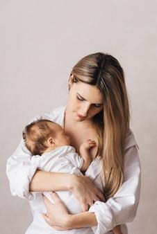 Une mère aimante porte son nouveau-né à la maison. portrait d'une mère heureuse tenant un bébé endormi dans ses bras. mère embrasse sa petite fille de 4 mois
