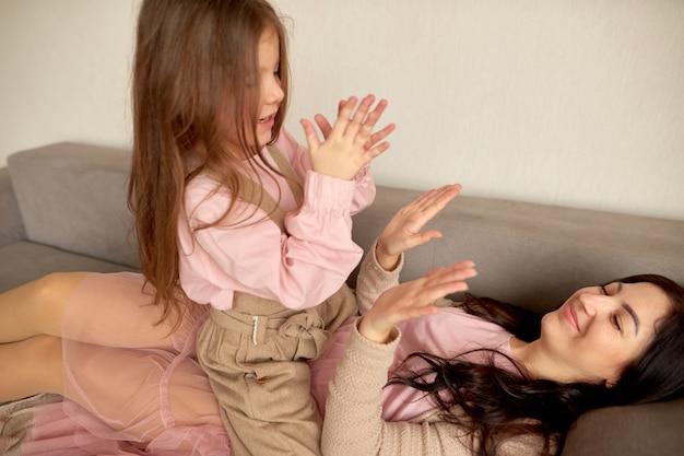 Mère aimante en riant jouer avec un enfant drôle mignon souriant. profiter du temps ensemble à la maison, maman célibataire de famille heureuse avec petite fille enfant s'amusant à jouer ressentir de la joie