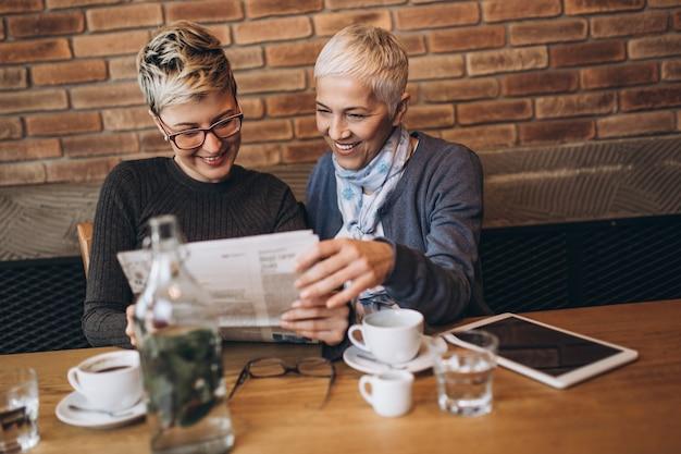 Mère aînée assise dans un café-bar ou un restaurant avec sa fille d'âge moyen, elles lisent les journaux et profitent de la conversation.