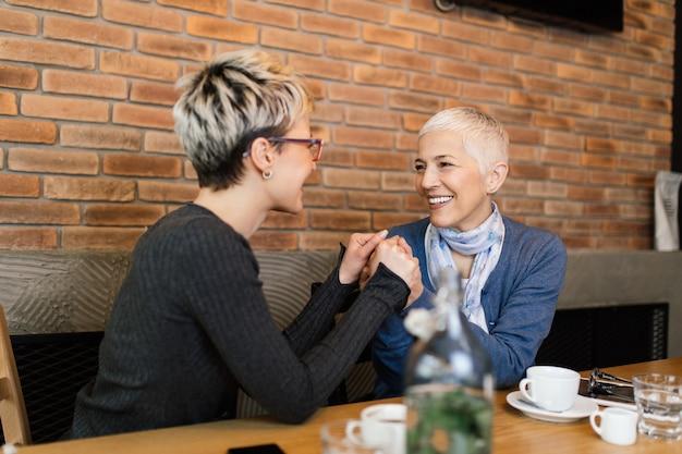 Mère aînée assise dans un café-bar ou un restaurant avec sa fille d'âge moyen et profitant de la conversation.