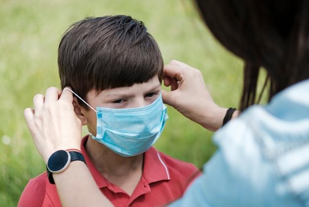 Mère ajustant un jeune garçon avec un masque facial
