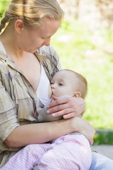 Une mère allaite son enfant dans le parc