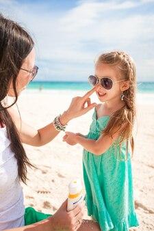 La mère applique une crème solaire sur son petit nez d'enfant