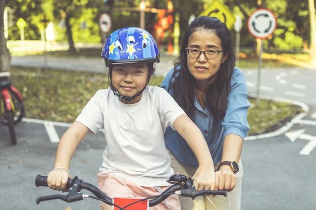 Mère apprenant à sa fille à faire du vélo dans le parc. famille en plein air à vélo.
