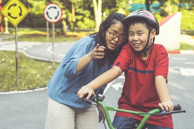 Mère apprenant à son soleil à faire du vélo dans le parc. famille en plein air à vélo.