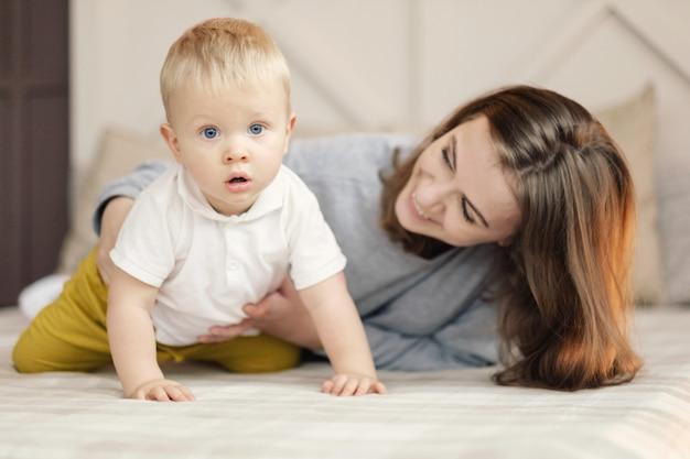 Mère apprend au bébé à ramper, heureuse mère et fils sur le lit