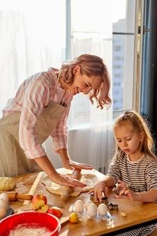 Mère apprend à sa fille à étaler de la pâte pour faire des biscuits, dans la cuisine à la maison