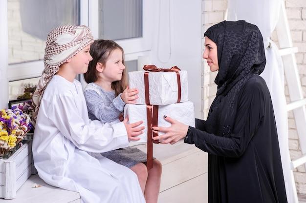 Mère arabe et enfants posant avec un cadeau. à l'intérieur.
