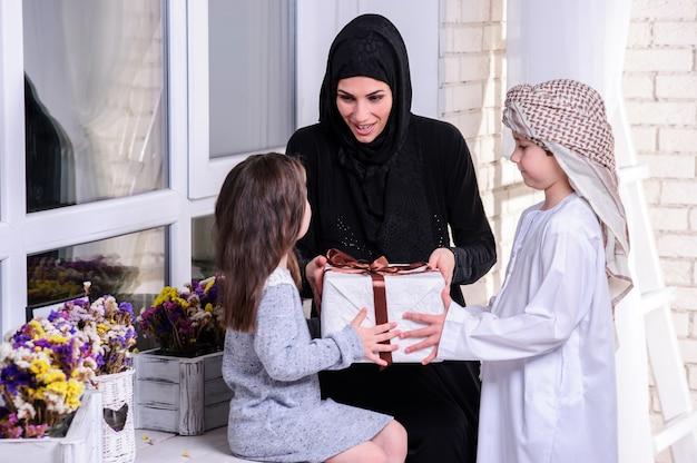 Mère arabe offrant un cadeau à ses enfants.