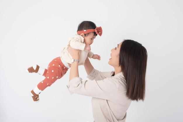 Mère asiatique et adorable petite fille sont heureux sur le mur blanc