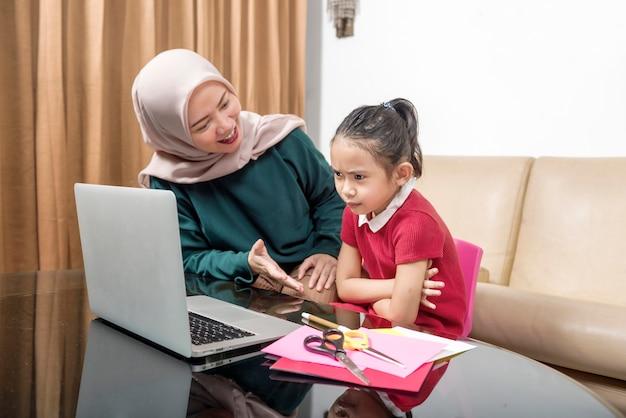 Mère asiatique aidant une petite fille à faire ses devoirs avec un ordinateur portable à la maison. éducation en ligne pendant la quarantaine