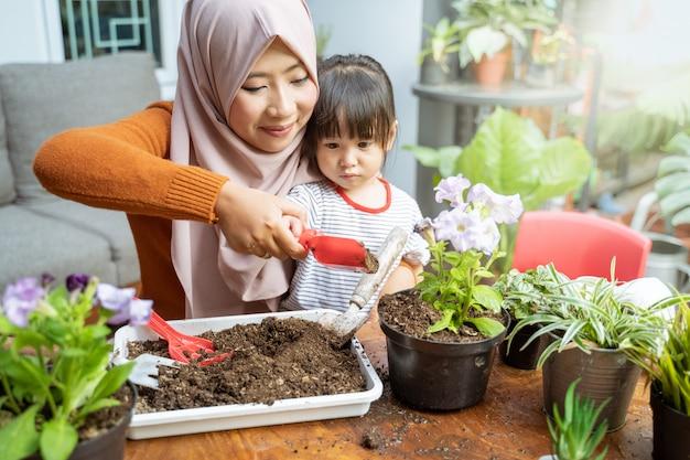 Une mère asiatique aide sa fille à tenir une petite pelle remplie de terre pour faire pousser des plantes en pot