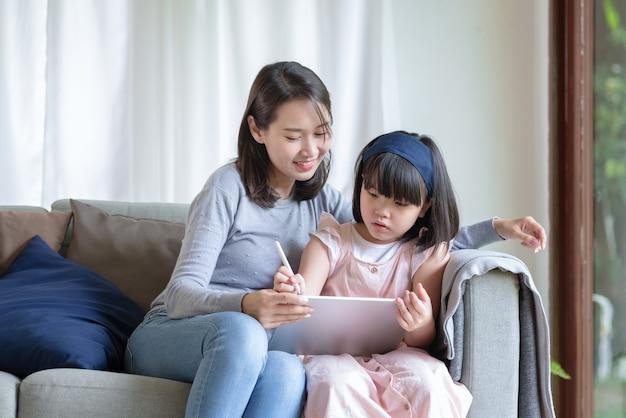 Une mère asiatique apprend à sa fille mignonne à étudier dans le salon à la maison