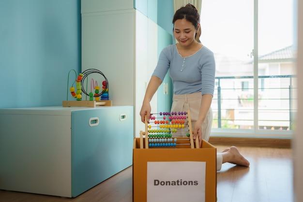 Une mère asiatique choisit les jouets de ses enfants qui ne jouent pas et met des boîtes de dons au centre de dons.