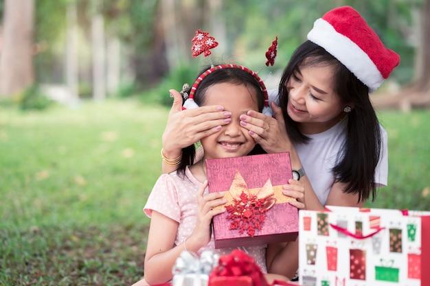 Une mère asiatique chuchote sa fille au jour de noël ou à noël