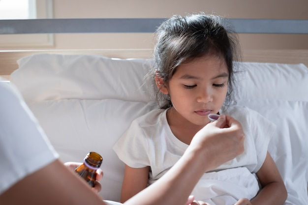 Mère asiatique donnant du sirop contre la toux sur une cuillère à sa fille au lit