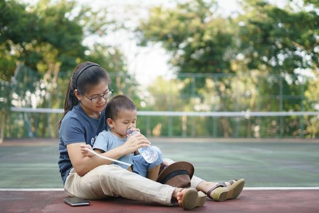 Mère asiatique donner un verre à son garçon