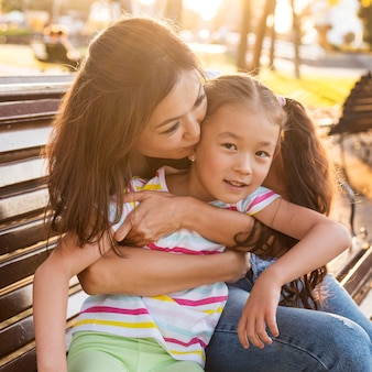 Mère asiatique embrassant son enfant sur la joue