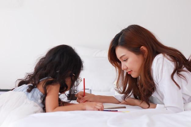 Une mère asiatique enseigne les devoirs à sa fille à la maison en vacances
