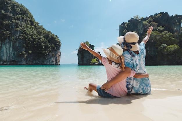 Mère asiatique et fille enfant assise sur la plage.