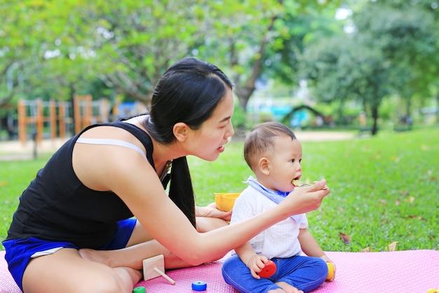 Mère asiatique nourrir les aliments pour bébé garçon assis sur un matelas rose dans le jardin.