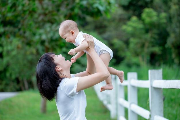 Mère asiatique portant son petit garçon. sourire et s'amuser ensemble.