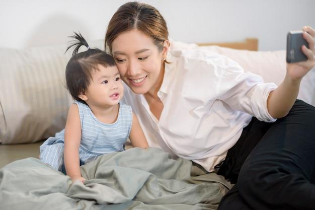 Mère asiatique et sa petite fille font un selfie ou un appel vidéo au père au lit.