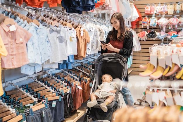 Mère asiatique avec son fils faisant du shopping dans le centre commercial tout en appelant au téléphone