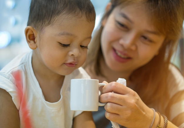 Mère asiatique et son fils. la mère a soulevé une tasse d'eau blanche.
