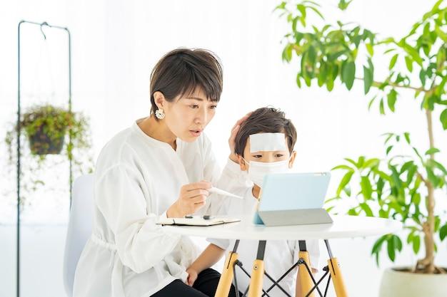 Une mère asiatique et son garçon seront examinés en ligne
