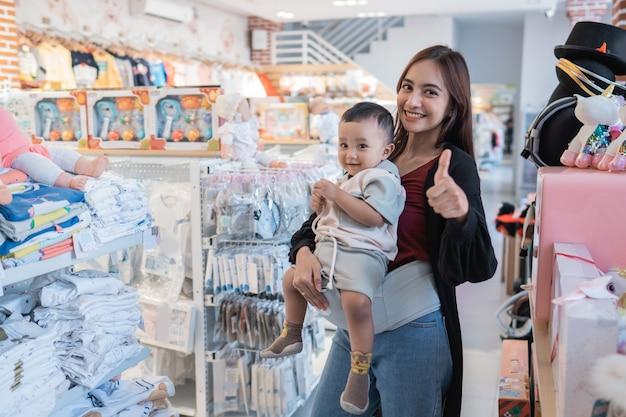 Mère asiatique avec son petit garçon faisant du shopping dans le magasin de bébé avec le pouce vers le haut