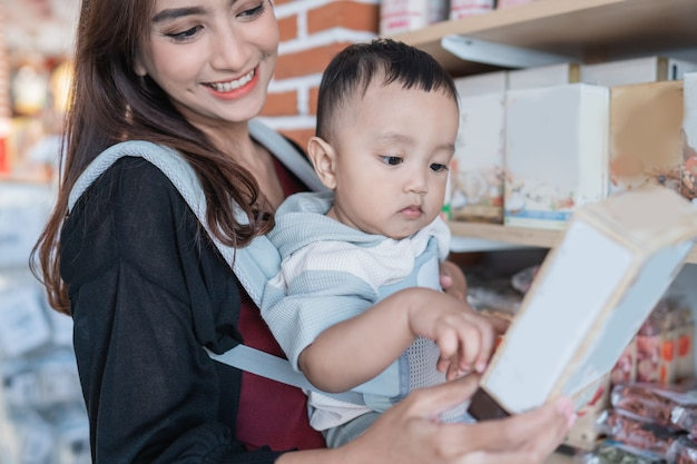 Mère asiatique avec son petit garçon faisant des emplettes dans le magasin de bébé