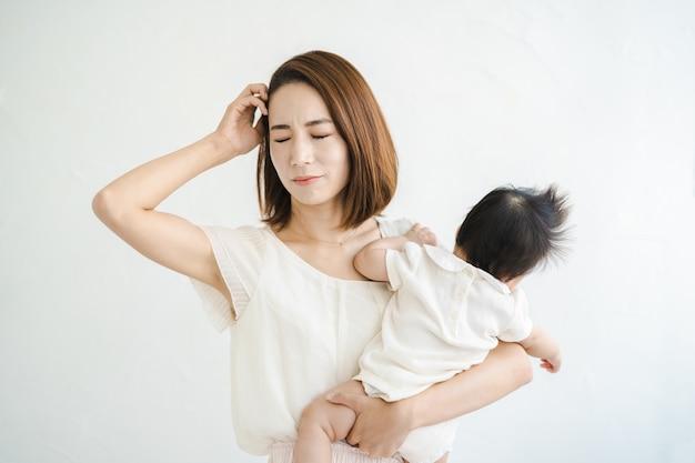 Mère asiatique tenant un bébé et ayant l'air fatigué