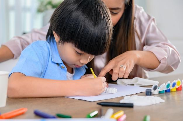 Une mère asiatique travaille à la maison avec son fils. image de dessin de maman et d'enfant et art de peinture de couleur. mode de vie de la femme et activité familiale.