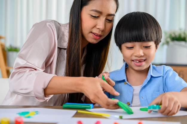 Une mère asiatique travaille à la maison avec son fils. maman et enfant jouent à la pâte. enfant créant un modèle en pâte à modeler. mode de vie de la femme et activité familiale.