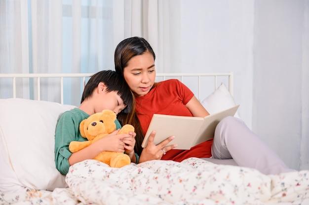 Une mère asiatique travaille à la maison avec son fils. maman et enfant lisant un conte de fées avant de dormir sur le lit. mode de vie de la femme et activité familiale.