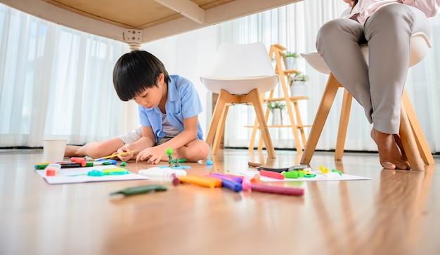 Une mère asiatique travaille à la maison avec son fils. maman travaille en ligne et enfant joue à la pâte sous la table. mode de vie de la femme et activité familiale.