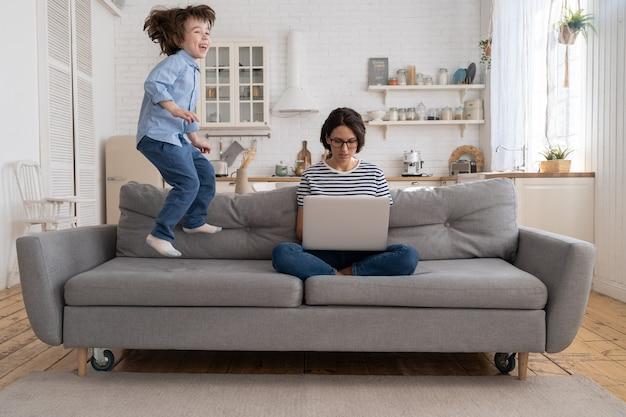 Mère assise sur le canapé travaille sur un ordinateur portable à la maison, essayant de se concentrer, l'enfant sautant et attirant l'attention