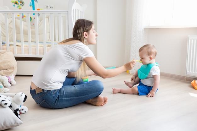 Mère assise par terre dans le salon et nourrissant son bébé avec de la bouillie