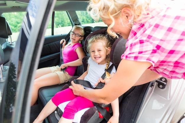Mère de l'attelage sur l'enfant dans le siège de sécurité de voiture