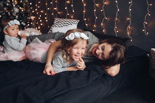 Mère attentionnée au lit avec ses adorables enfants avec des lumières de noël